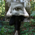 Untitled (self painted grey, cradling photograph of eye as a child, obscuring my own eyes, in front of backdrop held by partner), 116 x 85cm, Photograph mounted and box framed in black, 2016